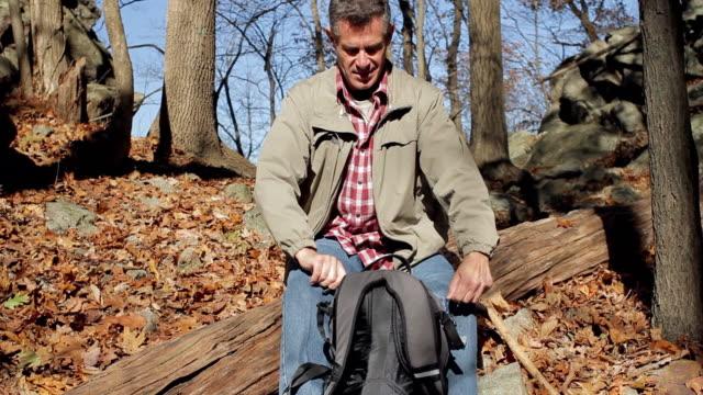 vidéos et rushes de ms td man pouring hot drink and resting on log during hike / clinton, new jersey, usa - seulement des hommes d'âge mûr