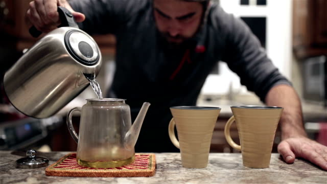 Mann gießen heißes Wasser in Tee Glas