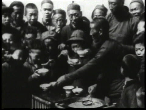 1932 WS Man pouring noodles into bowls for children and adults and they begin to eat / China