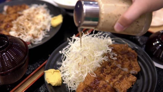 man pouring salad dressing with pork tonkatsu(japanese dish that consists of a breaded). - salad dressing stock videos & royalty-free footage