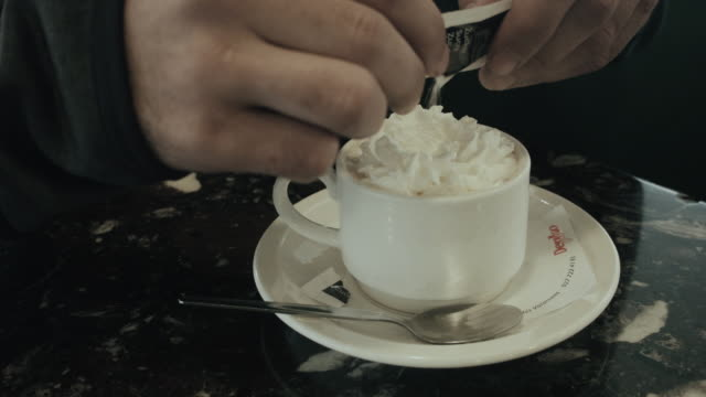 Man pouring sugar into hot chocolate with whipped cream