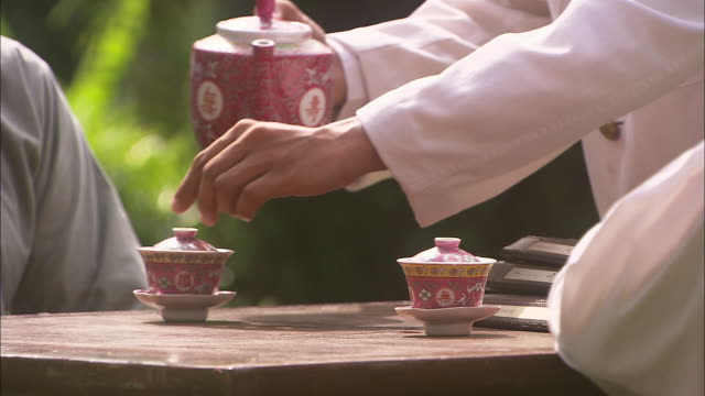 cu, pan, man pouring tea into two decorated cups, close-up of hands, singapore - unknown gender stock videos & royalty-free footage