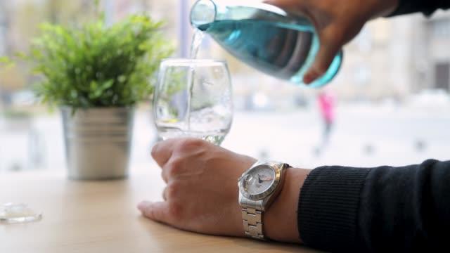 vídeos y material grabado en eventos de stock de el hombre que vierte agua forma botella en vidrio - agua potable