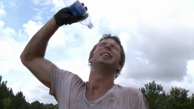 vídeos de stock e filmes b-roll de slo mo ms man pouring water on head from bottle / jacksonville, florida, usa - bater com a cabeça