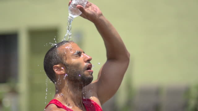 a man pouring water over his head and resting after a intense workout. - slow motion - bottiglia video stock e b–roll