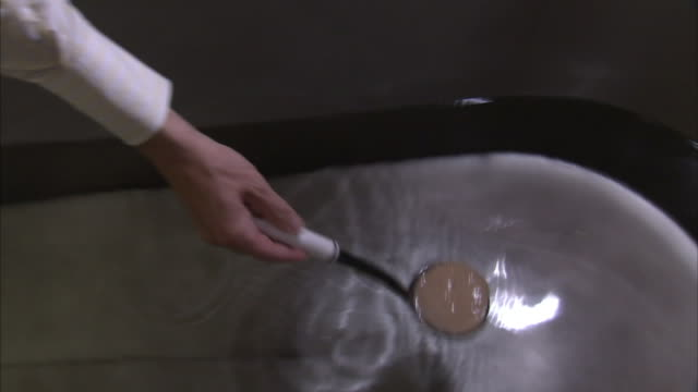 a man pours a liquid into a ladle then swishes it in a bathtub. - お玉点の映像素材/bロール
