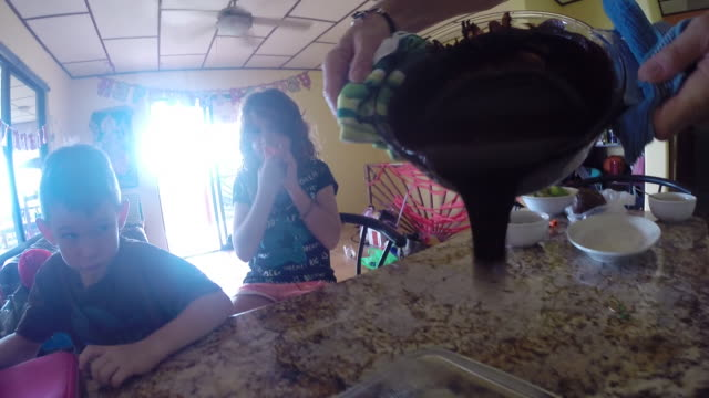 man pours chocolate out of bowl while girl and boy watch. - kelly mason videos 個影片檔及 b 捲影像