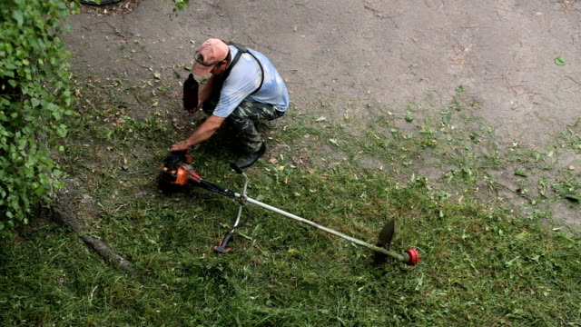 man pours gasoline into a lawn mower. - landscaped stock videos and b-roll footage