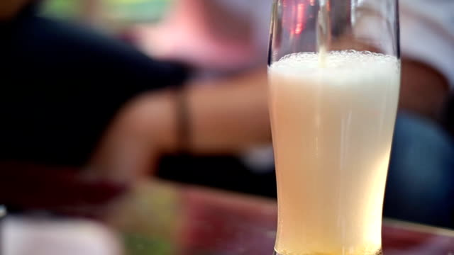 Man pours his beer Into the glass and drinks It