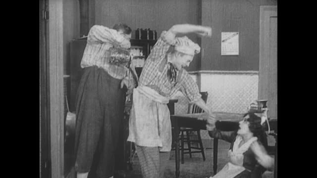 1917 man (fatty arbuckle) pours hot coffee down the knife wielding chef's pants to stop him from attacking a female servant - apron stock videos & royalty-free footage