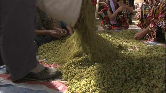 stockvideo's en b-roll-footage met a man pours raisins onto a pile in a courtyard in silk road china - rozijn