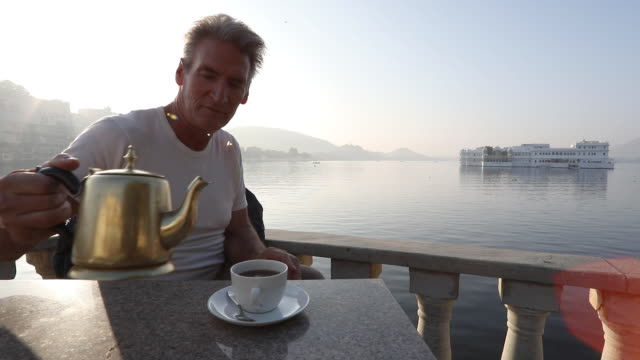 vídeos y material grabado en eventos de stock de hombre vierte té arriba a orillas del lago al amanecer - un solo hombre maduro