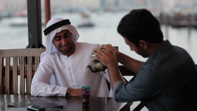 cu ms man pours tea for his arab friend in outdoor restaurant/dubai/uae - middle eastern culture stock videos and b-roll footage