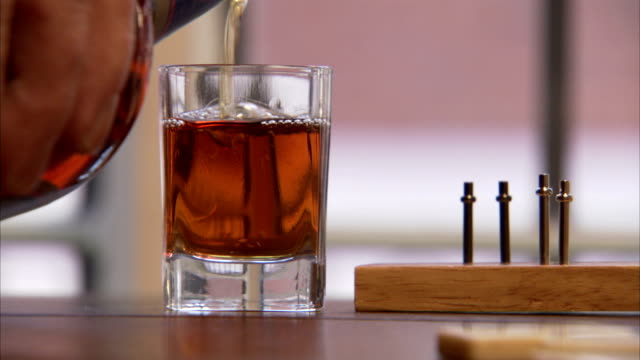 a man pours two shots of rum next to a peg board game. available in hd. - rum stock videos and b-roll footage