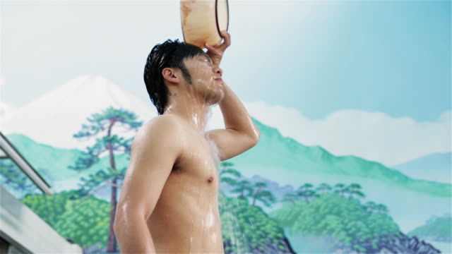 MS, LA A man pours water over his head in a traditional Japanese public bath house or sento / Tokyo, Japan