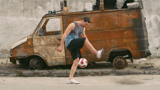 ms, slo mo a man practices football skills in a favela / rio de janeiro, brazil - juggling stock videos & royalty-free footage
