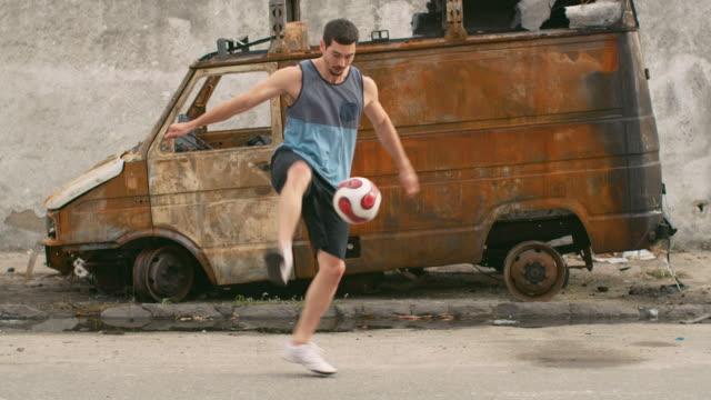 vídeos de stock, filmes e b-roll de ms, slo mo a man practices football skills in a favela / rio de janeiro, brazil - stunt