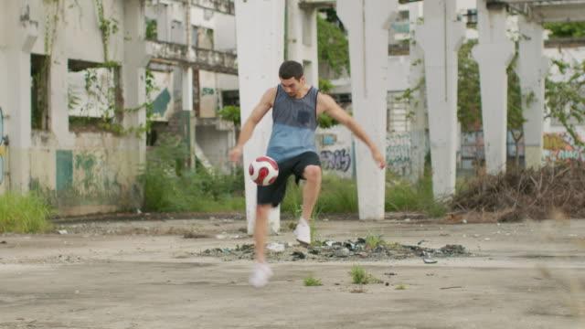 ms a man practices football skills in a favela / rio de janeiro, brazil - 練習点の映像素材/bロール