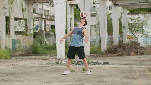 vídeos de stock, filmes e b-roll de ms a man practices football skills in a favela / rio de janeiro, brazil - stunt