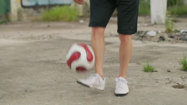 cu a man practices football skills in a favela / rio de janeiro, brazil - kicking stock videos & royalty-free footage