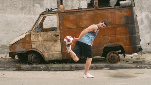 MS, SLO MO A man practices football skills in a favela / Rio de Janeiro, Brazil