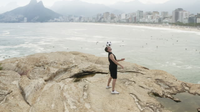 vídeos de stock, filmes e b-roll de ws, ts a man practices his football skills on ipanema beach - stunt