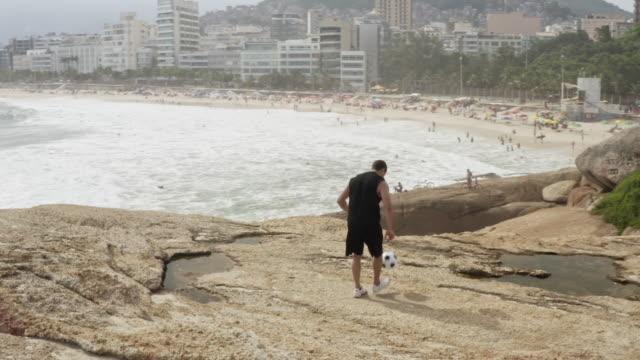 vídeos de stock, filmes e b-roll de ws, ts a man practices his football skills on ipanema beach - termo esportivo