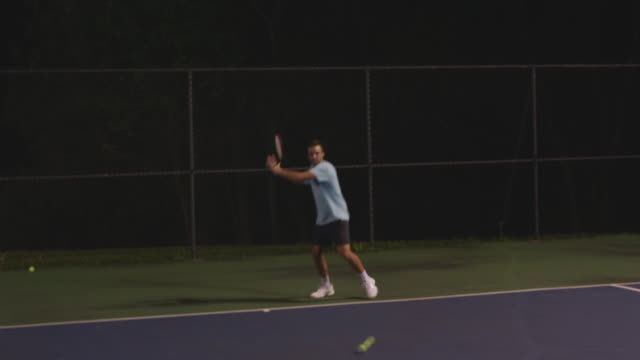 man practices volleys on tennis court at night, handheld - one mid adult man only stock videos & royalty-free footage