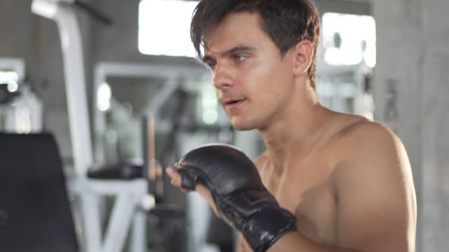 man practicing kick boxing in the gym in slow motion