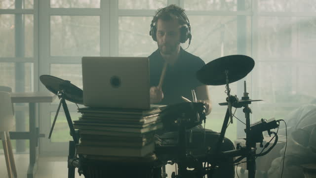 man practicing on electronic drums in a living room. looking at playing tutorial on a laptop - drummer stock videos & royalty-free footage