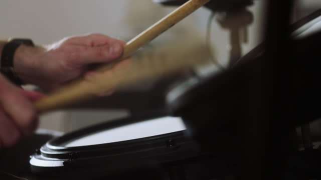 man practicing on electronic drums in his living room. close up on hands - drum kit stock videos & royalty-free footage