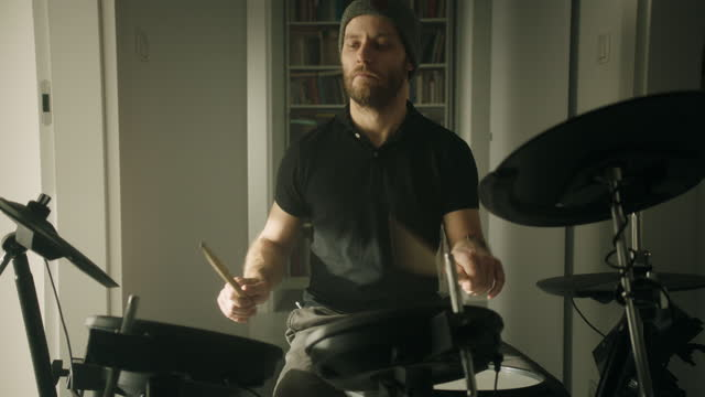 man practicing on electronic drums in his living room. front view - drum kit stock videos & royalty-free footage