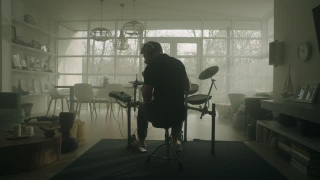 vídeos de stock e filmes b-roll de man practicing on electronic drums in his living room - artista