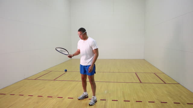WS PAN Man practicing racquetball in court, portrait / Santa Fe, New Mexico, USA