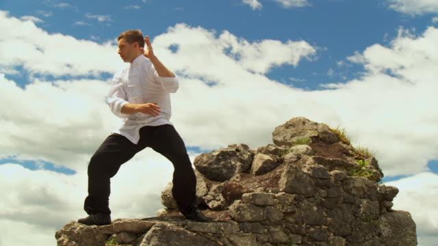 vídeos de stock e filmes b-roll de ws slo mo man practicing taijiquan on rocks of kamen castle / begunje na gorenjskem, slovenia - one mid adult man only