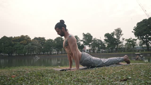 man practicing yoga in park - one mid adult man only stock videos & royalty-free footage