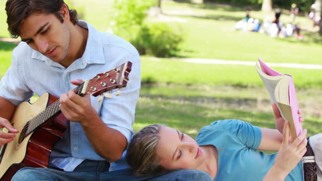 man practises on the guitar as the woman reads her book - auf der seite liegen stock-videos und b-roll-filmmaterial