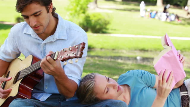 man practises guitar as the woman rests on his leg and reads - auf der seite liegen stock-videos und b-roll-filmmaterial