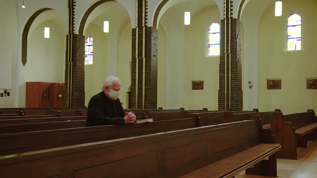 man praying in cathedral during pandemic - religion stock videos & royalty-free footage