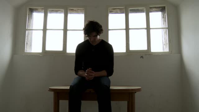 vídeos y material grabado en eventos de stock de ms man praying in front of church window with setting on wooden bench / dresden, saxony, germany - de cara al suelo