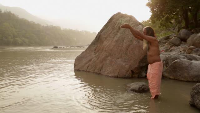 vídeos y material grabado en eventos de stock de man praying in the river ganges, rishikesh, uttarakhand, india - manos ahuecadas