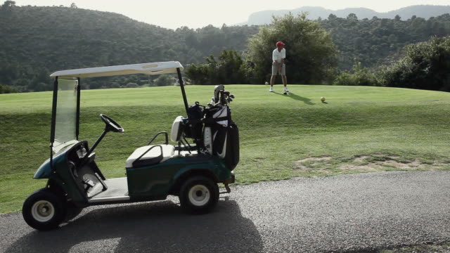 ws man prepares for golf swing at golf course, golf cart in foreground / palma de mallorca, mallorca, baleares, spain - golf cart stock videos & royalty-free footage