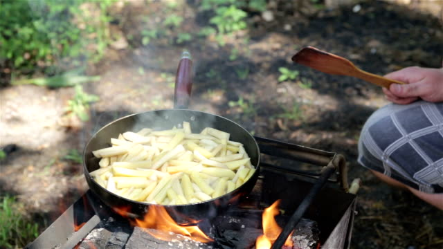 Man prepares fried potatoes on the campfire.
