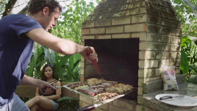 ms a man prepares meat on a barbecue / maringa, brazil - brazilian ethnicity stock videos & royalty-free footage