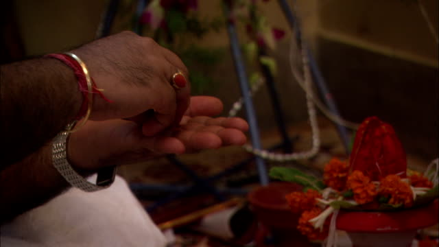 Man prepares offerings to Kali goddess for Diwali Hindu Festival of Lights. Available in HD.