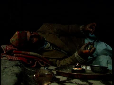 man prepares opium pipe inside squalid shack afghanistan - 掘建て小屋点の映像素材/bロール