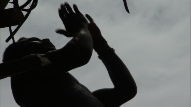 Man prepares to jump off wooden tower during land diving ritual, Pentecost, Vanuatu