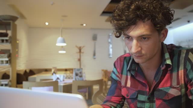 mann, die vorbereitung eines neuen projektes mit einem laptop. - gelockt stock-videos und b-roll-filmmaterial