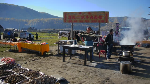 A Man Preparing and Boiling the Noodles in Hemu Village, Xinjiang Uygur Autonomous Region, China