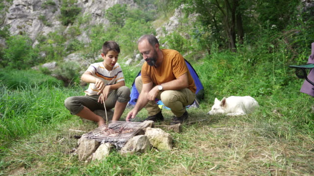 man preparing barbecue over open campfire with son - son stock videos & royalty-free footage